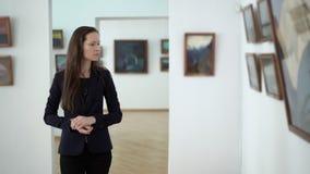 Έργα ζωγραφικής έργου της τέχνης στην έκθεση στο γκαλερί τέχνης πόλεων Η κομψή όμορφη γυναίκα εξετάζει τις εικόνες στο μουσείο φιλμ μικρού μήκους