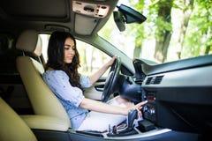 Έρευνα για την αγαπημένη μουσική Χαμογελώντας και ωθώντας κουμπιά νέων ελκυστικών γυναικών οδηγώντας το αυτοκίνητο στοκ εικόνες
