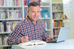 Έρευνα με το βιβλίο και το lap-top Στοκ Εικόνες