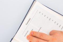 Έρευνα των πληροφοριών σε μια παχύ εγκυκλοπαίδεια ή ένα εγχειρίδιο βιβλίων στοκ εικόνα
