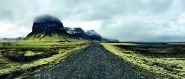 Έρημη μαύρη οδική κοπή μέσω του πράσινου ισλανδικού τοπίου Στοκ Φωτογραφία