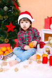 2 έτη αγοριών στο καπέλο Santa κάθονται κοντά στο χριστουγεννιάτικο δέντρο Στοκ φωτογραφία με δικαίωμα ελεύθερης χρήσης