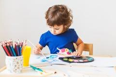 3 έτη ζωγραφικής κοριτσιών στο μικρό πίνακα στο σπίτι στοκ εικόνες με δικαίωμα ελεύθερης χρήσης