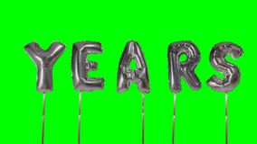 Έτη λέξης από τις ασημένιες επιστολές μπαλονιών ηλίου που επιπλέουν στην πράσινη οθόνη - απόθεμα βίντεο