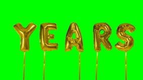 Έτη λέξης από τις χρυσές επιστολές μπαλονιών ηλίου που επιπλέουν στην πράσινη οθόνη - απόθεμα βίντεο