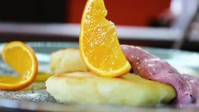 Έτοιμα cheesecakes με δύο σάλτσες και μια φέτα του πορτοκαλιού σε ένα πιάτο φιλμ μικρού μήκους