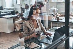 Έτοιμος να εργαστεί σκληρά Η τοπ άποψη της σύγχρονης νέας χρησιμοποίησης γυναικών υπολογίζει στοκ εικόνα