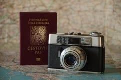 Έτοιμος να ταξιδεψει - κάμερα και διαβατήριο στο υπόβαθρο χαρτών tha Στοκ Εικόνες