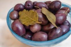 Έτοιμος να φάει τις μαύρες ελιές με τα πράσινα φύλλα στο πιάτο στοκ εικόνες
