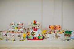 Έτοιμος πίνακας γενεθλίων για το κόμμα παιδιών Ζωηρόχρωμες καραμέλες στο επιτραπέζιο υπόβαθρο στοκ εικόνες