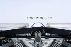 έτοιμος σταθερός Πηγαίνετε δεμένες με ταινία σύνθημα λέξεις σε μια εκλεκτής ποιότητας γραφομηχανή στοκ φωτογραφίες