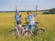 Έφηβη και αγόρι σε ένα ποδήλατο σε έναν θερινό τομέα της σίκαλης Στοκ Εικόνες