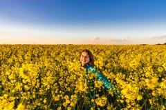 Έφηβη με μακρυμάλλη στον κίτρινο τομέα bittercress Στοκ Φωτογραφία