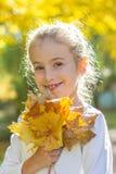Έφηβη με τα κίτρινα φύλλα σφενδάμου στοκ φωτογραφία