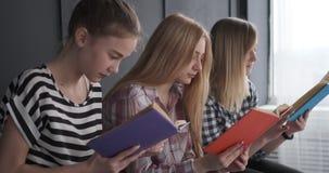 Έφηβη που έχουν τη διασκέδαση διαβάζοντας τα βιβλία απόθεμα βίντεο
