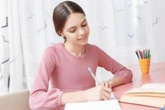 Έφηβη που γράφει στο βιβλίο άσκησής της Στοκ εικόνα με δικαίωμα ελεύθερης χρήσης