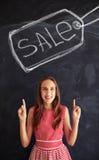 Έφηβη που δείχνει επάνω με τους δείκτες στο μεγάλο σημάδι πώλησης που σύρεται Στοκ Εικόνες
