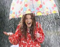 Έφηβη που προφυλάσσει από τη βροχή κάτω από την ομπρέλα Στοκ Εικόνες
