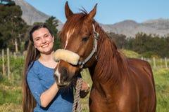 Έφηβη που στέκεται με το αραβικό άλογο κάστανών της που εξετάζει τη κάμερα στοκ φωτογραφίες με δικαίωμα ελεύθερης χρήσης