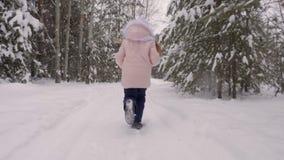 Έφηβη που τρέχει μέσω του χιονώδους δάσους απόθεμα βίντεο
