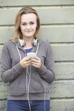 Έφηβη που φορά τα ακουστικά και που ακούει τη μουσική σε αστικό στοκ εικόνα