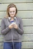 Έφηβη που φορά τα ακουστικά και που ακούει τη μουσική σε αστικό στοκ φωτογραφίες με δικαίωμα ελεύθερης χρήσης