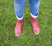 Έφηβη που φορά τις κόκκινες λαστιχένιες μπότες Στοκ Εικόνα