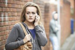 Έφηβη που χρησιμοποιεί το τηλέφωνο όπως αισθάνεται εκφοβισμένη στο σπίτι περιπάτων στοκ φωτογραφία