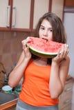Έφηβη στην πορτοκαλιά μπλούζα που δαγκώνει μια φέτα του καρπουζιού στοκ φωτογραφία με δικαίωμα ελεύθερης χρήσης