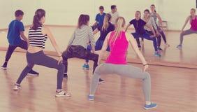 Έφηβοι και κορίτσια με το τέντωμα εκπαιδευτών στην αίθουσα χορού Στοκ Εικόνα