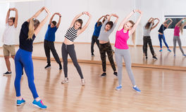 Έφηβοι και κορίτσια με το τέντωμα εκπαιδευτών στην αίθουσα χορού Στοκ εικόνα με δικαίωμα ελεύθερης χρήσης