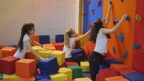 Έφηβοι κοριτσιών που έχουν τη διασκέδαση στο κέντρο τραμπολίνων σε έναν σωρό των πολύχρωμων μαλακών κύβων φιλμ μικρού μήκους