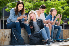 Έφηβοι που εξετάζουν τα τηλέφωνά τους στο πάρκο Στοκ Εικόνα