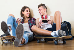 Έφηβοι που κάθονται στο πάτωμα με τα κινητά τηλέφωνα Στοκ Εικόνες