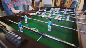 Έφηβοι που παίζουν το επιτραπέζιο ποδόσφαιρο Νέοι γραφείων που απολαμβάνουν το παιχνίδι επιτραπέζιου ποδοσφαίρου απόθεμα βίντεο