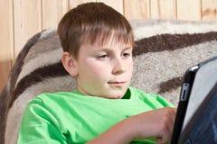 Έφηβος αγοριών με τον υπολογιστή ταμπλετών Στοκ Φωτογραφίες