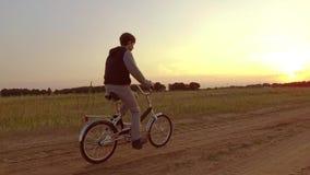 Έφηβος αγοριών που οδηγά ένα ποδήλατο Ο έφηβος αγοριών που οδηγά ένα ποδήλατο πηγαίνει στη φύση κατά μήκος της τηλεοπτικής πυροβο Στοκ Φωτογραφία