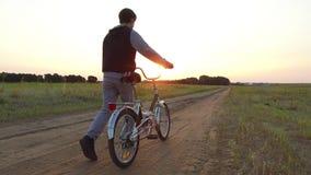Έφηβος αγοριών που οδηγά ένα ποδήλατο Το οδηγώντας ποδήλατο εφήβων αγοριών πηγαίνει φύση κατά μήκος του βίντεο κινήσεων πορειών s Στοκ Φωτογραφίες