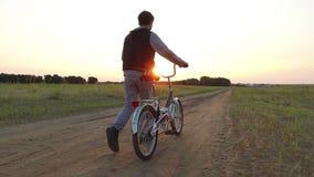 Έφηβος αγοριών που οδηγά ένα ποδήλατο Το οδηγώντας ποδήλατο εφήβων αγοριών πηγαίνει φύση κατά μήκος του βίντεο κινήσεων πορειών s Στοκ Φωτογραφία