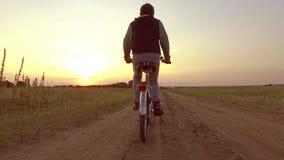 Έφηβος αγοριών που οδηγά ένα ποδήλατο Ο έφηβος αγοριών που οδηγά ένα ποδήλατο πηγαίνει στη φύση κατά μήκος της τηλεοπτικής πυροβο απόθεμα βίντεο