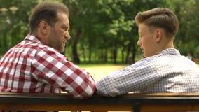 Έφηβος γιος που μιλά με τον πατέρα στον πάγκο στο πάρκο, μπαμπάς που υποστηρίζει το παιδί του φιλμ μικρού μήκους