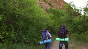 Έφηβος δύο που ταξιδεύει με τα σακίδια πλάτης στα βουνά απόθεμα βίντεο