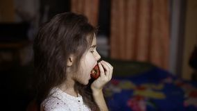 Έφηβος κοριτσιών που τρώει μια συνεδρίαση μήλων στο δωμάτιο το βράδυ απόθεμα βίντεο