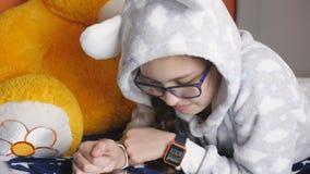 Έφηβος κοριτσιών που χρησιμοποιεί την ηλεκτρονική ταμπλέτα που βρίσκεται στον καναπέ σε θερμά PJ απόθεμα βίντεο