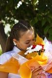 Έφηβος κοριτσιών σε μια άσπρη μπλούζα που ρουθουνίζει μια ανθοδέσμη των τριαντάφυλλων και Στοκ Φωτογραφία