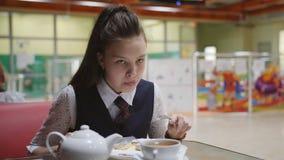 Έφηβος κοριτσιών σε μια συνεδρίαση σχολικών στολών σε έναν πίνακα στη σχολική καφετέρια που τρώει τα κέικ και που πίνει το τσάι απόθεμα βίντεο