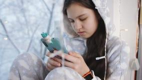 Έφηβος κοριτσιών στις θερμές πυτζάμες στην ανάγνωση χειμερινών παραθύρων σε ένα smartphone φιλμ μικρού μήκους