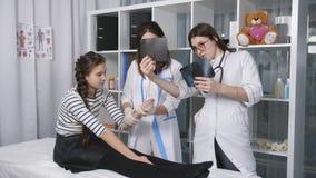 Έφηβος κοριτσιών στο γραφείο του γιατρού του traumotology Οι γιατροί εξετάζουν τις ακτίνες X των χεριών του ασθενή μικρών κοριτσι φιλμ μικρού μήκους