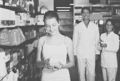 Έφηβος κοριτσιών στο φαρμακείο που επιλέγει τα προϊόντα υγειονομικής περίθαλψης στοκ εικόνες