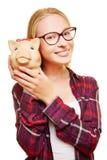 Έφηβος με τα γυαλιά και piggy τράπεζα Στοκ φωτογραφία με δικαίωμα ελεύθερης χρήσης